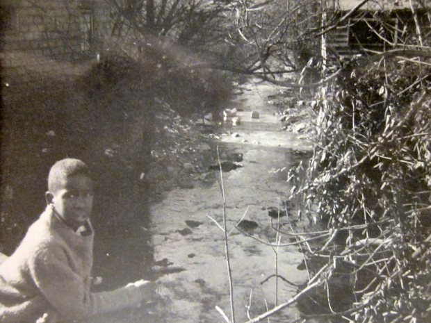 A young man leaning on the railing over Nasty Branch at South French Broad Avenue in the mid-1960s. ((From the HACA archives in the Special Collections, Ramsey Library, UNC-Asheville)