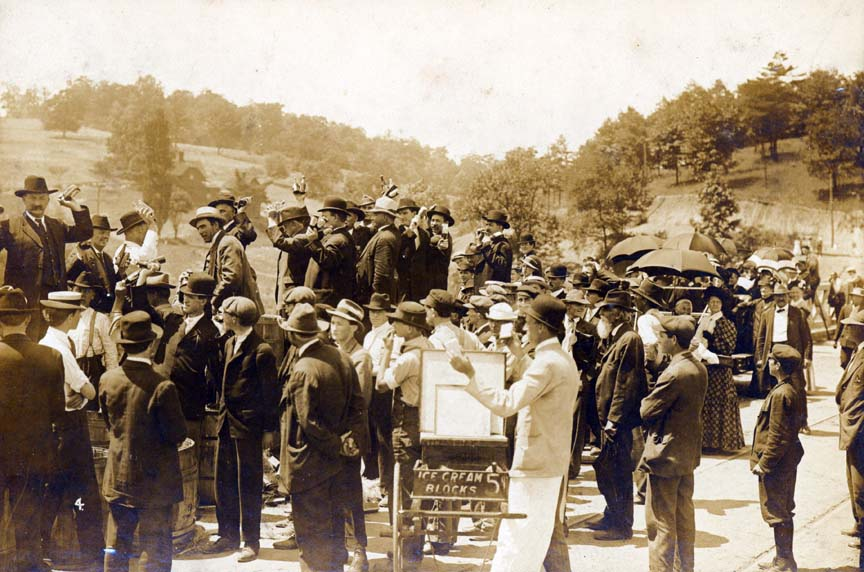 At a rally in support of prohibition, men prepare to throw bottles into the French Broad River from the side of the bridge at Riverside Park.